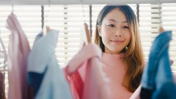 bella giovane signora asiatica attraente che sceglie i suoi vestiti di vestito di moda nell'armadio a casa o in negozio. ragazza pensa a cosa indossare camicia casual. guardaroba di casa o spogliatoio del negozio di abbigliamento. foto