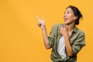 ritratto di giovane donna asiatica sorridente con espressione allegra, mostra qualcosa di straordinario in uno spazio vuoto in abbigliamento casual e in piedi isolato su sfondo giallo. concetto di espressione facciale. foto