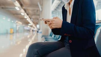 la donna d'affari asiatica indossa la tuta seduta con la valigia e usa il messaggio di chat dello smartphone in panchina aspetta il volo all'aeroporto. pendolare di viaggio d'affari nella pandemia di covid, concetto di viaggio d'affari. foto