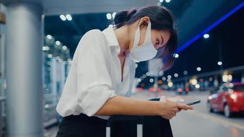 la ragazza d'affari asiatica arriva a destinazione indossa la maschera per il viso sta fuori guarda lo smartphone aspetta il terminal dell'auto all'aeroporto nazionale. pandemia di covid per pendolari d'affari, concetto di distanza sociale di viaggio d'affari. foto