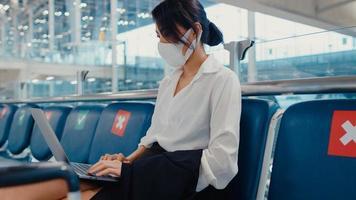 la donna d'affari asiatica che viaggia indossa la maschera per il viso seduta in panchina usa il laptop per lavorare tra l'attesa del volo nel terminal dell'aeroporto. pendolare di viaggio d'affari nella pandemia di covid, concetto di viaggio d'affari. foto