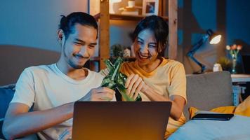 felice giovane coppia asiatica godersi l'evento della festa notturna online sedersi sul divano usa il computer portatile videochiamata con gli amici brindare bevendo birra tramite videochiamata online nel soggiorno di casa, concetto di distanza sociale. foto