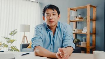il giovane uomo d'affari asiatico che utilizza il computer portatile parla con i colleghi del piano in una riunione di videochiamata mentre lavora da casa in soggiorno. autoisolamento, distanziamento sociale, quarantena per il virus corona. foto