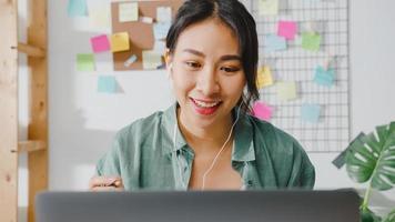 donna d'affari asiatica che utilizza laptop parla con i colleghi del piano in videochiamata mentre lavora in modo intelligente da casa in soggiorno. autoisolamento, distanziamento sociale, quarantena per la prevenzione del virus corona. foto