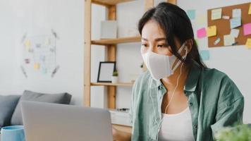donna d'affari asiatica che indossa una maschera medica utilizzando il laptop parla con i colleghi del piano in videochiamata mentre lavora da casa in soggiorno. distanziamento sociale, quarantena per la prevenzione del virus corona. foto