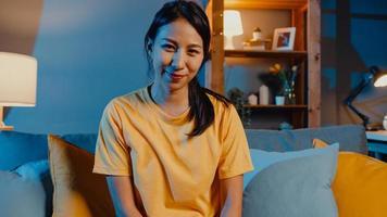 felice giovane donna asiatica freelance che guarda l'obbiettivo sorridente e allegra rilassarsi durante la videochiamata online di notte nel soggiorno di casa, stare a casa in quarantena, lavorare da casa, concetto di distanza sociale. foto