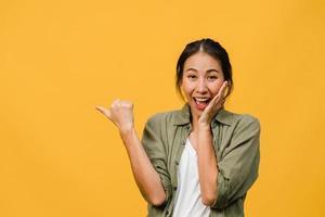ritratto di giovane donna asiatica sorridente con espressione allegra, mostra qualcosa di straordinario nello spazio vuoto in un panno casual e guardando la telecamera isolata su sfondo giallo. concetto di espressione facciale. foto