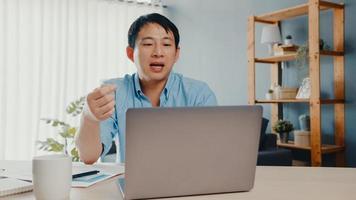 giovane uomo d'affari asiatico che utilizza laptop parla con i colleghi del piano in videochiamata mentre lavora in modo intelligente da casa in soggiorno. autoisolamento, distanziamento sociale, quarantena per la prevenzione del virus corona. foto