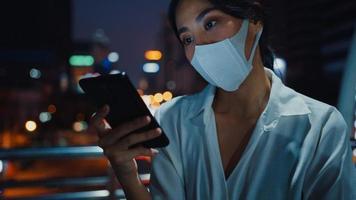 giovane imprenditrice asiatica in abiti alla moda che indossa la maschera facciale utilizzando lo smartphone digitando un messaggio di testo mentre si sta all'aperto nella città urbana di notte. distanziamento sociale per prevenire la diffusione del concetto di covid-19. foto
