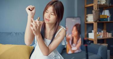 felice giovane ragazza asiatica trucco vlog anteriore della fotocamera del telefono godere di revisione rossetto parlare con seguace nel soggiorno a casa. stile di vita dell'attività di blogger, concetto di pandemia di coronavirus a distanza sociale. foto