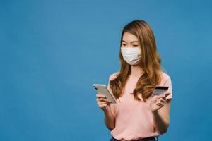 giovane donna asiatica che indossa una maschera medica utilizzando il telefono e la carta di credito con espressione positiva, sorride ampiamente, vestita con abiti casual e stand isolato su sfondo blu. foto