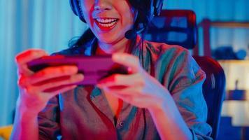 felice asia ragazza giocatore indossa la competizione per le cuffie gioca al videogioco online con smartphone luci al neon colorate nel soggiorno di casa. gioco in streaming di esport online, concetto di attività di quarantena domestica. foto