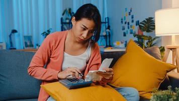 la signora asiatica si sente stressata e preoccupata per la fattura e la fattura della carta di credito che calcolano il prestito sul divano di casa. stress del mutuo per la casa, ottenere un prestito senza lavoro, prestiti per situazioni di disagio per il coronavirus, non è possibile effettuare il concetto di pagamento del prestito. foto