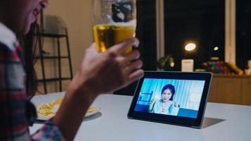 giovane signora asiatica che beve birra divertendosi momento felice festa notturna evento celebrazione online tramite videochiamata nel soggiorno di casa di notte. distanziamento sociale, quarantena per la prevenzione del coronavirus. foto