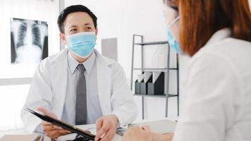 il medico maschio asiatico serio indossa una maschera protettiva usando il tablet sta offrendo grandi discorsi di notizie discutono risultati o sintomi con una paziente nell'ufficio dell'ospedale. stile di vita nuovo normale dopo il virus corona. foto