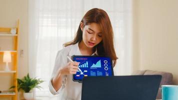 donna d'affari asiatica che utilizza laptop e tablet presentazione ai colleghi sul piano in videochiamata mentre si lavora da casa in soggiorno. autoisolamento, distanziamento sociale, quarantena per coronavirus. foto