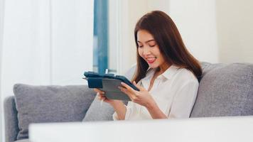 giovane donna d'affari asiatica che utilizza la videochiamata tablet parlando con la famiglia mentre lavora da casa in soggiorno. autoisolamento, distanza sociale, quarantena per coronavirus nel prossimo concetto normale. foto