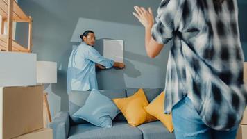 felice asiatico giovane coppia attraente uomo e donna si aiutano a vicenda appendere la cornice sul muro decorare la casa e il pacchetto della scatola di cartone nel soggiorno. giovane sposato asiatico che decora il concetto di casa. foto