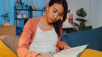 notte bella signora asiatica leggere il libro con felicità nel tranquillo soggiorno sul divano. educazione da casa, soggiorno a casa, attività di autoquarantena, attività divertente per la quarantena di covid o coronavirus. foto