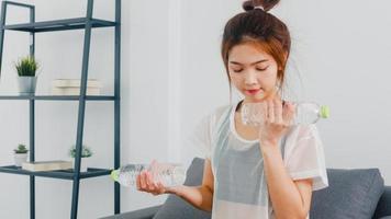 giovane donna coreana in esercizi di abbigliamento sportivo facendo allenamento utilizzando manubri leggeri con bottiglia d'acqua sul divano nel soggiorno di casa. distanza sociale, isolamento durante il virus, stare a casa. foto