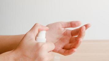 donna asiatica che usa disinfettante per le mani spray alcolico per lavare le mani per proteggere il coronavirus. la femmina spinge la bottiglia di alcol per pulire la mano per l'igiene quando il distanziamento sociale rimane a casa e il tempo di autoquarantena. foto
