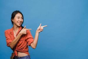 ritratto di giovane donna asiatica sorridente con espressione allegra, mostra qualcosa di straordinario in uno spazio vuoto in abbigliamento casual e in piedi isolato su sfondo blu. concetto di espressione facciale. foto