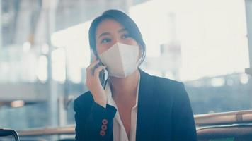 smart asian business girl indossare tuta seduta con valigia in panchina chiamata smart phone parlare con il partner in attesa del volo in aeroporto. pendolare di viaggio d'affari nella pandemia di covid, concetto di viaggio d'affari. foto