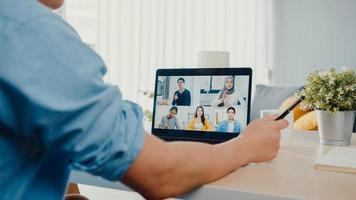il giovane uomo d'affari asiatico che utilizza il laptop parla con i colleghi del piano in una riunione di videochiamata mentre lavora da casa in soggiorno. autoisolamento, distanziamento sociale, quarantena per la prevenzione del virus corona. foto