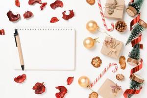 minimo piatto creativo laici della composizione tradizionale natalizia invernale e delle festività natalizie di capodanno. vista dall'alto mockup aperto taccuino nero per il testo su sfondo bianco. simulare e copiare la fotografia spaziale. foto