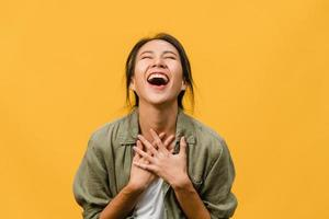 la giovane donna asiatica si sente felice con l'espressione positiva, gioiosa sorpresa funky, vestita con un panno casual isolato su sfondo giallo. felice adorabile donna felice esulta successo. espressione facciale. foto