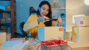 la giovane donna asiatica usa lo smartphone per scattare una foto del codice a barre sul prodotto del pacco per la consegna della spedizione al cliente in ufficio a casa di notte. piccola impresa, consegna del mercato online, concetto di lifestyle freelance.