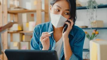 le giovani donne d'affari asiatiche indossano la maschera facciale utilizzando la chiamata del telefono cellulare che riceve l'ordine di acquisto e controllano il prodotto sul lavoro di magazzino a casa. piccolo imprenditore, concetto freelance di consegna del mercato online. foto