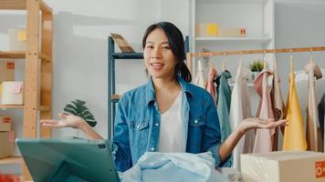 giovane stilista di moda donna asiatica che utilizza il telefono cellulare riceve l'ordine di acquisto e mostra i vestiti che registrano video in streaming live online presso il negozio. piccolo imprenditore, concetto di consegna del mercato online. foto