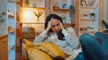 la premurosa signora asiatica che soffre di insonnia si siede sul divano nel soggiorno di notte a casa con sentirsi sola, triste e depressa adolescente trascorre del tempo da sola resta a casa, distanza sociale, quarantena del coronavirus. foto