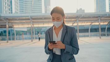 la giovane donna d'affari asiatica in abiti da ufficio alla moda indossa una maschera medica usando il telefono mentre cammina da sola all'aperto nella città urbana. affari in movimento, distanza sociale per prevenire la diffusione del concetto di covid-19. foto