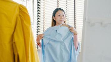 bella signora asiatica attraente che sceglie i vestiti sulla medicazione dello stendibiancheria che si guarda allo specchio in camera da letto a casa. ragazza pensa a cosa indossare camicia casual. le donne di stile di vita si rilassano a casa concetto. foto