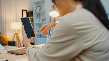la giovane donna asiatica usa lo smartphone con lo schermo nero vuoto finto display per il testo pubblicitario mentre lavora in modo intelligente da casa nel soggiorno di notte. tecnologia chiave di crominanza, concetto di design di marketing. foto