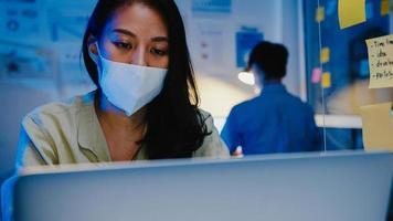 felice donna d'affari asiatica che indossa una maschera medica per il distanziamento sociale in una nuova situazione normale per la prevenzione dei virus mentre si utilizza il laptop al lavoro durante la notte in ufficio. vita e lavoro dopo il coronavirus. foto