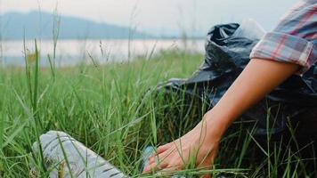felici giovani attivisti asiatici che raccolgono rifiuti di plastica nella foresta. le volontarie coreane aiutano a mantenere la natura pulita e a raccogliere la spazzatura. concetto sui problemi di inquinamento di conservazione ambientale. foto