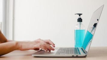 donna asiatica che usa un disinfettante in gel alcolico lavarsi le mani prima di lavorare sul laptop per proteggere il coronavirus. le donne spingono l'alcol a pulire per l'igiene quando il distanziamento sociale rimane a casa e il tempo di autoquarantena. foto