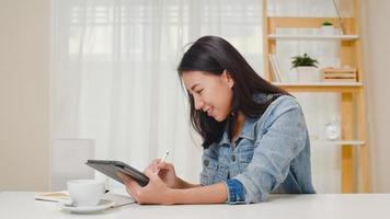 freelance graphic designer donne abbigliamento casual utilizzando tavoletta grafica digitale disegno sul posto di lavoro nel soggiorno di casa. felice giovane ragazza asiatica rilassarsi seduto sulla scrivania fare un lavoro in internet. foto