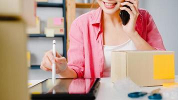 giovane imprenditrice asiatica che utilizza una chiamata di telefonia mobile che riceve l'ordine di acquisto e controlla il prodotto in magazzino, lavora a casa in ufficio. piccolo imprenditore, consegna al mercato online, concetto di lifestyle freelance. foto