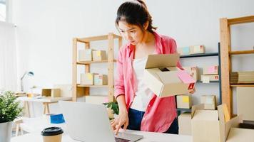 giovane imprenditrice asiatica imprenditrice controlla l'ordine di acquisto del prodotto in magazzino e salva sul computer portatile lavoro a casa ufficio. piccolo imprenditore, consegna al mercato online, concetto di lifestyle freelance. foto