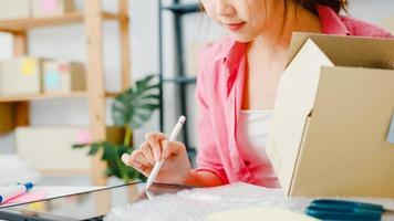 giovane imprenditrice asiatica imprenditrice controlla l'ordine di acquisto del prodotto in magazzino e salva sul computer tablet lavora a casa ufficio. piccolo imprenditore, consegna al mercato online, concetto di lifestyle freelance. foto