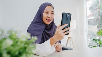 giovane donna d'affari musulmana asiatica che utilizza lo smartphone parla con un amico tramite videochat brainstorming riunione online mentre lavora a distanza da casa in soggiorno. distanziamento sociale, quarantena per il virus corona. foto
