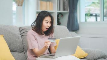 donna asiatica che utilizza computer portatile e carta di credito per lo shopping e-commerce, la donna si rilassa sentendosi felice dello shopping online seduto sul divano nel soggiorno di casa. le donne di stile di vita si rilassano a casa concetto. foto