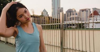 bella giovane donna atleta dell'asia si esercita facendo stretching in ambiente urbano. ragazza adolescente giapponese che indossa abiti sportivi sul ponte pedonale al mattino presto. stile di vita sportivo attivo in città. foto
