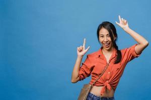 ritratto di giovane donna asiatica sorridente con espressione allegra, mostra qualcosa di straordinario nello spazio vuoto in un panno casual e guardando la telecamera isolata su sfondo blu. concetto di espressione facciale. foto