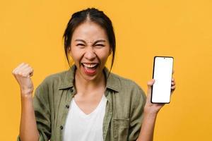 la giovane donna asiatica mostra lo schermo dello smartphone vuoto con un'espressione positiva, sorride ampiamente, vestita con abiti casual sentendosi felici su sfondo giallo. telefono cellulare con schermo bianco in mano femminile. foto