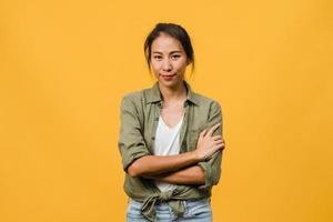 ritratto di giovane donna asiatica con espressione positiva, braccia incrociate, sorriso ampiamente, vestita con abiti casual e guardando la telecamera su sfondo giallo. felice adorabile donna felice esulta successo. foto